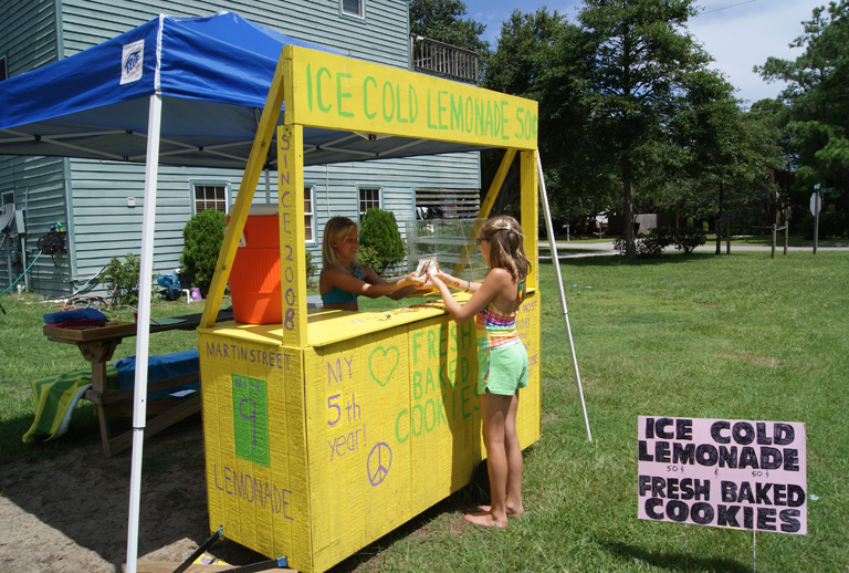Cassidy Joyce with a customer at her lemonade stand on Martin St. in
