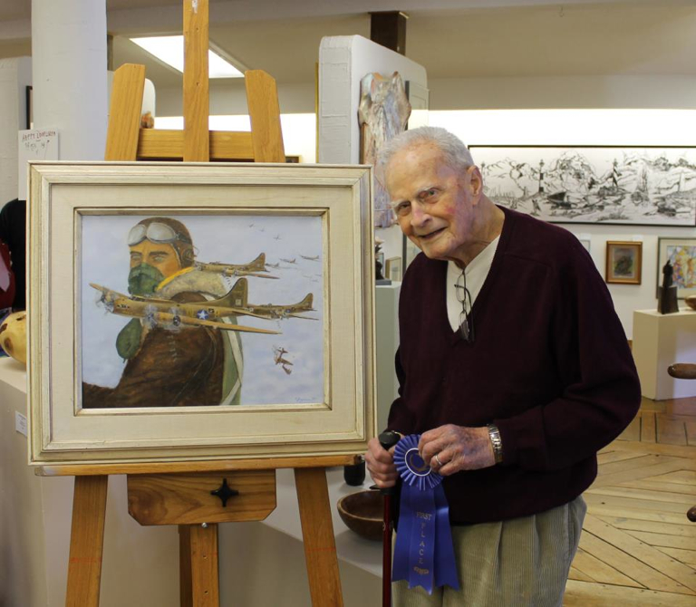 Don Bryan with prize winning painting, Raid on Regensburg, at Ghost Fleet Gallery's self-portrait show in April.