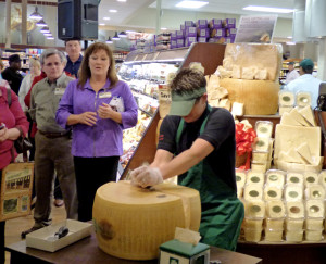 Pam Rosencrans crack a wheel of Parmigiano-Reggiano--signifying the grand opening.