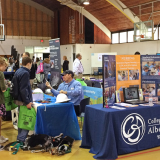 Students milling around booths at STEM Fair at the Roanoke Island campus of COA.