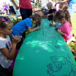 Decorating the Farmdog Surfboard at the 25th Annual DCAC Artrageous.