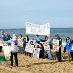Organizing on the beach for a group photo. The signs from Ocracoke were brought out of the closet from the attempt in the 1990s to lease oil/gas sites off North Carolina.