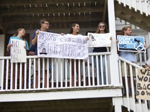 Members of the Manteo High School Environmental Action Committee holding up signs after being told to leave the sidewalk.