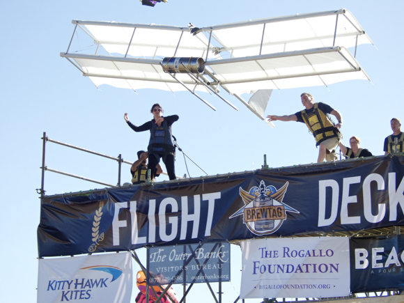 Outer Banks Visitors Bureau launching their Wright Flyer. The glider seemed to be in flight longer than any other, although it did not qualify by distance. Standing on the edge to the left is Allison Wyant. Pushing the tail is Aaron Tuell, Amy Wood to his right and Bruce Weaver of Kitty Hawk Kites.