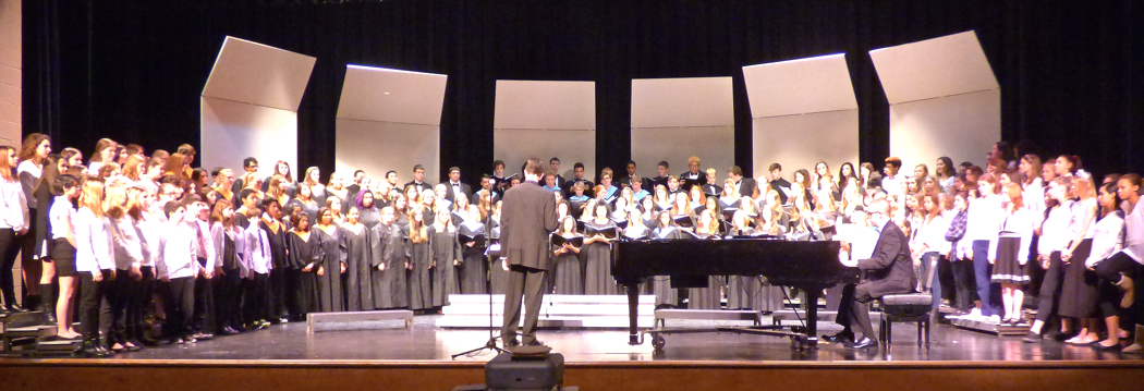 "Combined choirs performing ""We Are the Children"" at First Flight High School."