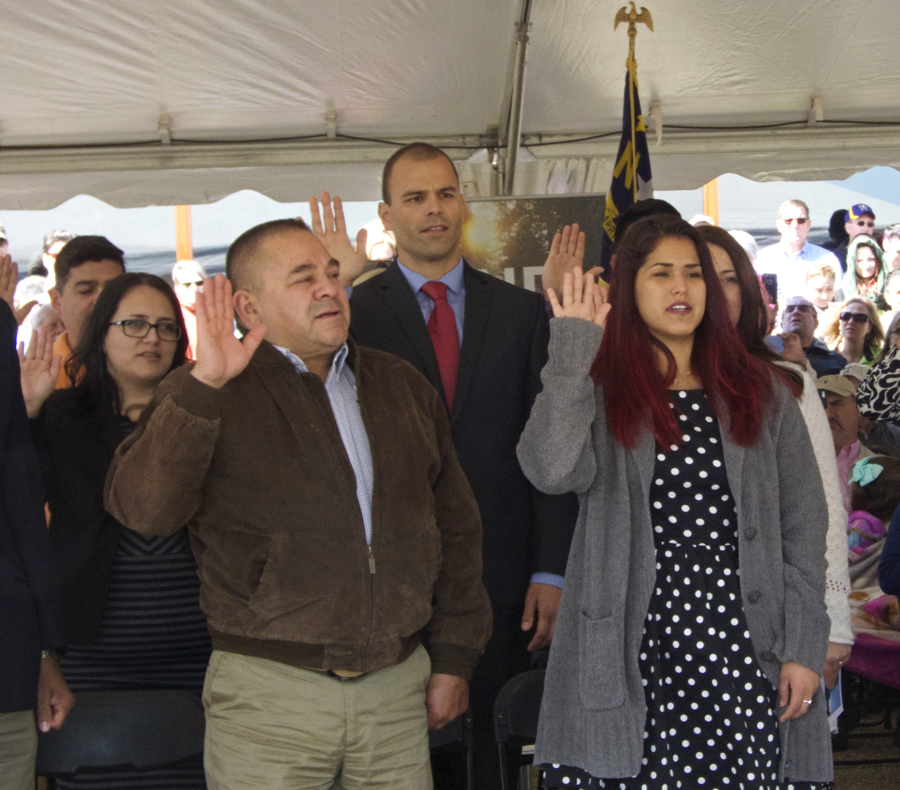Hands raised to become the newest US citizens. Raul Campos in brown jacket, Fabiano Menezes de Souza wearing a red tie, and Juliana Vaca-Triperri in the black and white dress.