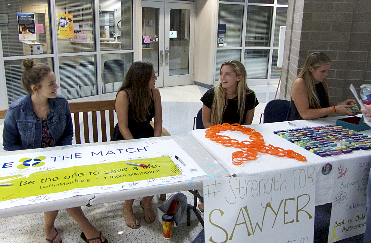 Helping to pay for treatment and research. First Flight High School students man Sawyer's support table.
